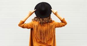 Kall flickasikt från baksida som bär en svart hatt, solglasögon och omslaget royaltyfri bild