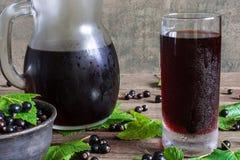 Kall fruktsaft för svart vinbär i ett exponeringsglas och en kanna Arkivbild