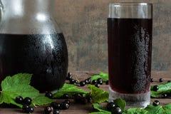 Kall fruktsaft för svart vinbär i ett exponeringsglas och en kanna på trätabellen Royaltyfria Bilder