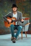 Kall grabb med hatten som spelar gitarren på grå bakgrund royaltyfria bilder