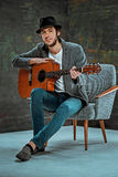 Kall grabb med hatten som spelar gitarren på grå bakgrund fotografering för bildbyråer