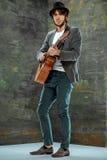 Kall grabb med hatten som spelar gitarren på grå bakgrund arkivfoton
