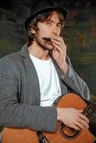 Kall grabb med hatten som spelar gitarren på grå bakgrund arkivfoto