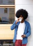 Kall grabb som dricker kaffe och använder mobiltelefonen Royaltyfri Foto