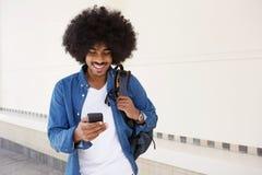 Kall grabb som går med mobiltelefonen och påsen Arkivfoton
