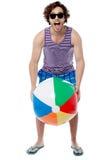 Kall grabb som spelar med strandbollen arkivbild