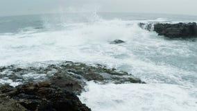 Kall havbränning på Rocky Shore långsam rörelse arkivfilmer