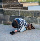Kall hemlös man på hans knä som tigger för pengar från turister på Charles Bridge i Prague - vår 2019 royaltyfria bilder