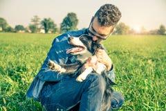 Kall hund som spelar med hans ägare arkivfoto