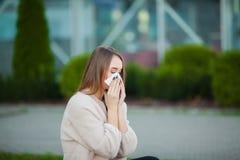 kall influensa Den unga attraktiva flickan, fångade en förkylning på gatan, torkar hennes näsa med en servett royaltyfri bild