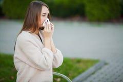kall influensa Den unga attraktiva flickan, fångade en förkylning på gatan, torkar hennes näsa med en servett royaltyfria bilder