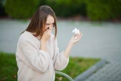 kall influensa Den unga attraktiva flickan, fångade en förkylning på gatan, torkar hennes näsa med en servett arkivfoto