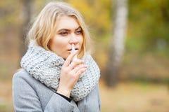 kall influensa Den unga sjuka kvinnan använder en nässprej på gatan utanför arkivfoto