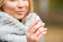 kall influensa Den unga sjuka kvinnan använder en nässprej på gatan utanför royaltyfri foto