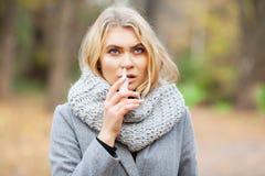kall influensa Den unga sjuka kvinnan använder en nässprej på gatan utanför royaltyfri fotografi