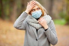 kall influensa Kvinna med en medicinsk framsidamaskering på utomhus- royaltyfri foto