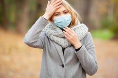 kall influensa Kvinna med en medicinsk framsidamaskering på utomhus- arkivbild