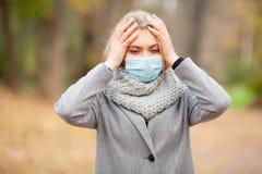 kall influensa Kvinna med en medicinsk framsidamaskering på utomhus- royaltyfria foton