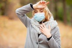 kall influensa Kvinna med en medicinsk framsidamaskering på utomhus- fotografering för bildbyråer