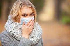 kall influensa Kvinna med en medicinsk framsidamaskering på utomhus- arkivbilder