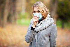 kall influensa Kvinna med en medicinsk framsidamaskering på utomhus- royaltyfria bilder