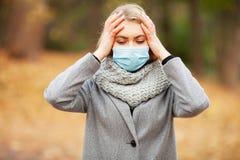 kall influensa Kvinna med en medicinsk framsidamaskering på utomhus- royaltyfri bild