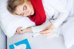 kall influensa Sjuk kvinna som ligger på en säng med en termometer fotografering för bildbyråer