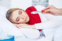 kall influensa Sjuk kvinna som ligger på en säng med en termometer royaltyfri bild