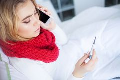 kall influensa Sjuk kvinna som ligger på en säng med en termometer arkivfoton