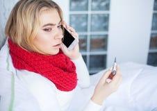 kall influensa Sjuk kvinna som ligger på en säng med en termometer royaltyfri foto