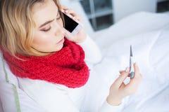 kall influensa Sjuk kvinna som ligger på en säng med en termometer arkivbild