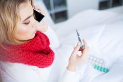 kall influensa Sjuk kvinna som ligger på en säng med en termometer arkivbilder