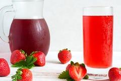 Kall jordgubbefruktsaft i ett exponeringsglas och en kanna Royaltyfria Foton