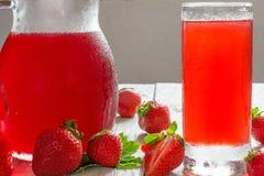 Kall jordgubbefruktsaft i ett exponeringsglas och en kanna på den vita trätabellen Royaltyfria Foton