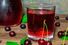 Kall körsbärsröd fruktsaft i ett exponeringsglas och en kanna på trätabellen med mogna bär omkring Arkivbilder