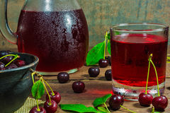 Kall körsbärsröd fruktsaft i ett exponeringsglas och kannan på trätabellen med mogna bär i krukmakeri bowlar Arkivfoton
