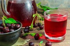 Kall körsbärsröd fruktsaft i ett exponeringsglas och kannan på trätabellen med mogna bär i krukmakeri bowlar Arkivfoto