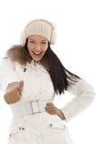 Kall kvinna med tummen upp på vintertid Arkivfoto