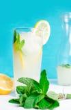 Kall lemonad med mintkaramellen och citronen på en blå bakgrund Arkivfoto