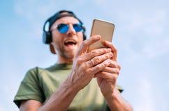 Kall man i baseballmössa, trådlös hörlurar och blå solglasögon som bläddrar i hans för playlistssmartphone för spelare mp3 appara arkivfoto