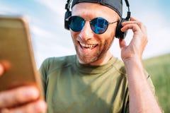 Kall man i baseballmössa, trådlös hörlurar och blå solglasögon som bläddrar i hans för playlistssmartphone för spelare mp3 appara royaltyfri bild