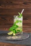 Kall mojitococtail med rom, mintkaramellen, iskuber och limefrukt i ett highballexponeringsglas på träbakgrunden alkoholiserad dr Arkivfoto