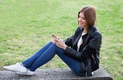 Kall nätt kvinna med mobilen Fotografering för Bildbyråer