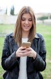 Kall nätt kvinna med mobilen Royaltyfri Fotografi