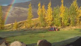 Kall orange höstmorgondimma med regnbågen och tältet i bergen stock video