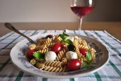 Kall pasta med den mini- mozzarellaen, den körsbärsröda tomaten, basilikasidor, svarta oliv och rosévin Cerasuoloe royaltyfri foto