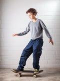 Kall pojke på hans skateboard Arkivbild