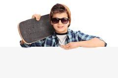 Kall pojke som rymmer en skateboard bak panel Arkivfoton
