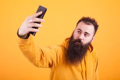 Kall skäggig man som bär den gula hoodien och tar selfie över gul bakgrund fotografering för bildbyråer