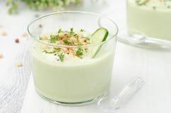 Kall soppa med avokadot, gurkan och yoghurt i en glass dryckeskärl arkivbild